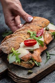 Sándwich, tostadas con salmón, queso crema, parmesano, alcaparras, tomates cherry y rúcula. imagen vertical. vista superior,