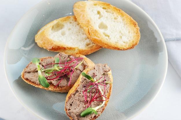Sandwich de tostadas tostadas con paté y hierbas en un plato azul
