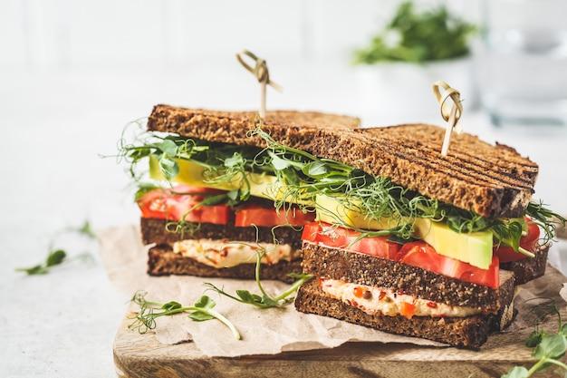 Sandwich vegano con tofu, hummus, aguacate, tomate y brotes.