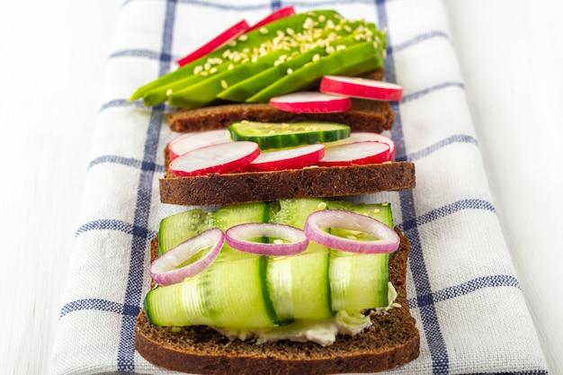 Sándwich vegetariano abierto de superalimento con diferentes ingredientes: aguacate, pepino, rábano sobre tela. alimentación saludable. comida orgánica y vegetariana. cerrar, copiar espacio para texto