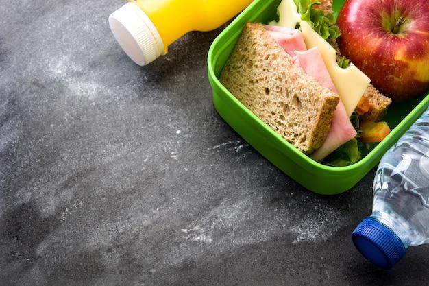 Sandwich, verduras y frutas en pizarra