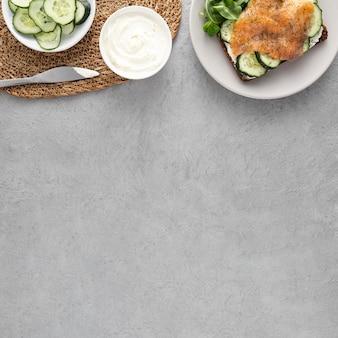Sándwich de vista superior con pepinos y salmón en un plato con espacio de copia