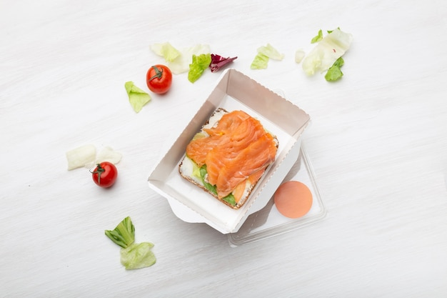Sándwich de vista superior con queso blando y pescado rojo se encuentra en la lonchera junto a las verduras y tomates en una mesa blanca. concepto de merienda saludable.