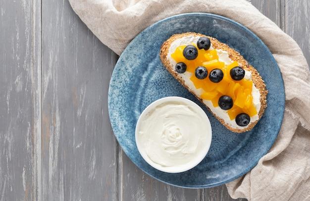 Sándwich de vista superior con queso crema y frutas en un plato