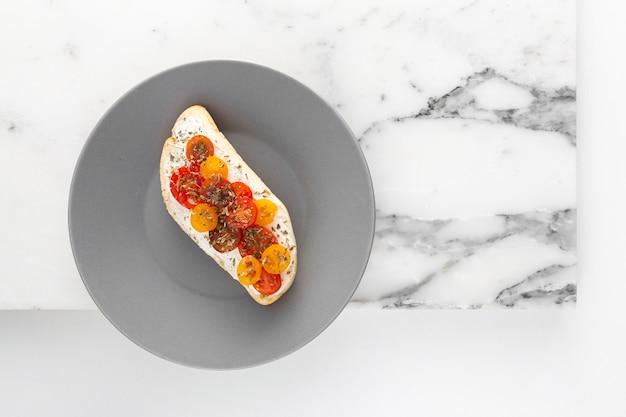 Sándwich de vista superior con queso crema y tomates en placa