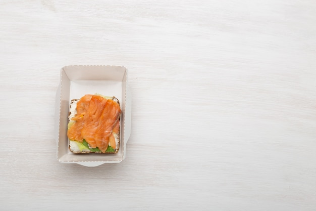 Sándwich de vista superior con queso tierno y pescado rojo se encuentra en la lonchera junto a las verduras y tomates sobre un fondo blanco con espacio de copia. concepto de merienda saludable.