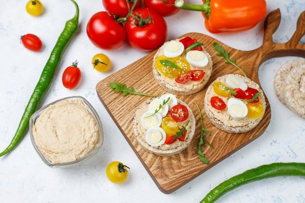Sándwiches abiertos de pasteles de arroz con hummus, verduras y huevo de codorniz, desayuno o almuerzo saludable.