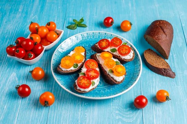 Sándwiches abiertos con requesón, tomates cherry y albahaca.