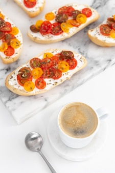 Sándwiches de alto ángulo con queso crema y tomates con café