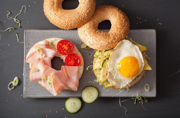 Sandwiches en bagels con huevo, aguacate, queso blando, brotes de alfalfa, jamón, tomate
