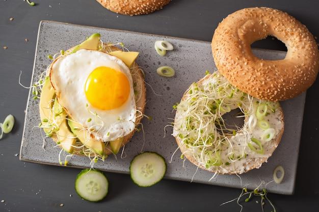 Sandwiches en bagels con huevo, aguacate, queso blando, brotes de alfalfa