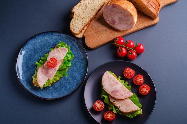 Sándwiches con carne de jamón de pavo, ensalada verde y rodajas de tomates cherry frescos en un plato negro y azul cerca de los ingredientes en la tabla de cortar, pared mínima azul, vista superior