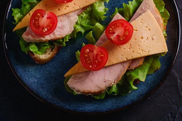Sándwiches con carne de jamón de pavo, queso, ensalada verde y rodajas de tomates cherry frescos en placa azul, pared con textura oscura, vista superior macro