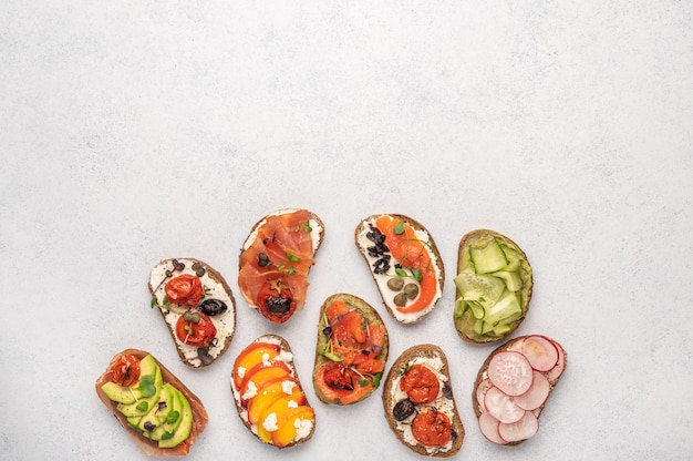 Sándwiches caseros con pan y diversos ingredientes y especias en un espacio luminoso. comida deliciosa y saludable para el desayuno y el almuerzo.