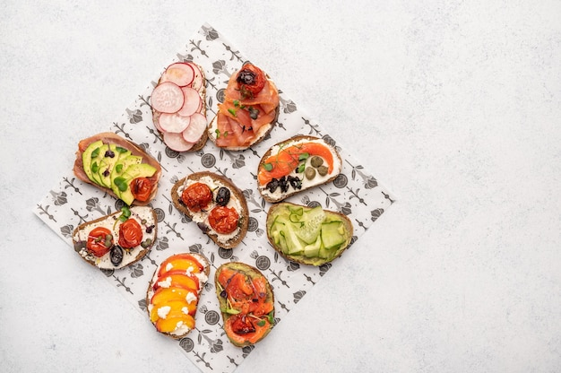 Sándwiches caseros con pan y diversos ingredientes y especias en un papel artesanal. comida deliciosa y saludable para el desayuno y el almuerzo.