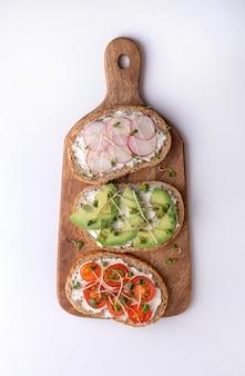 Sandwiches de cereales con microgreens, rábanos, aguacates y tomates en una tabla de cortar sobre una superficie blanca