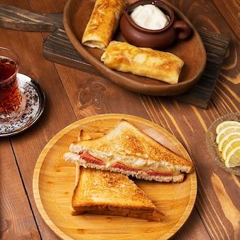 Sándwiches de club con salami, tocino y blinchik servidos con yogurt en un plato de madera con té