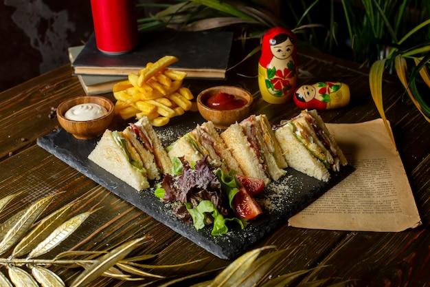 Sándwiches club servidos con papas fritas ketchup y mayonesa