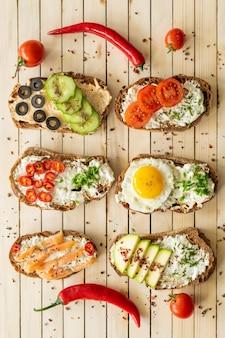 Sándwiches de composición con verduras salmón y huevo sobre un fondo de madera nutrición adecuada