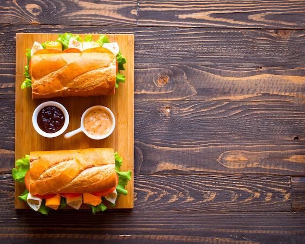 Sándwiches deliciosos y sabrosos con pavo, jamón, queso, tomates sobre fondo de madera
