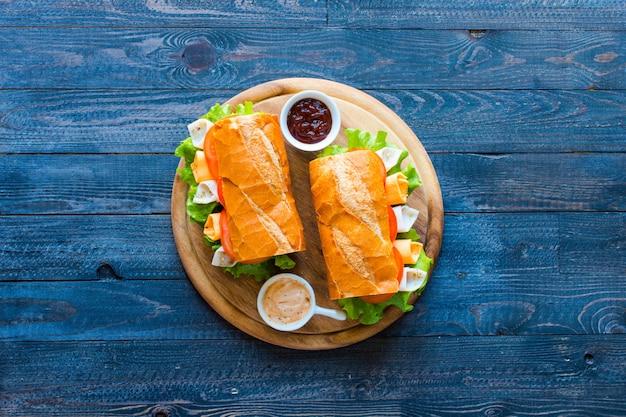 Sándwiches deliciosos y sabrosos con pavo, jamón, queso, tomates.