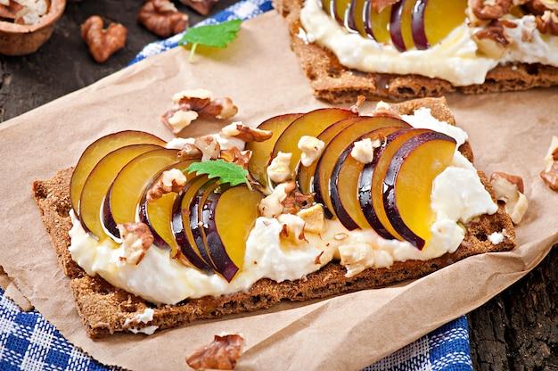 Sandwiches de dieta vegetariana pan crujiente con queso cottage, ciruelas, nueces y miel