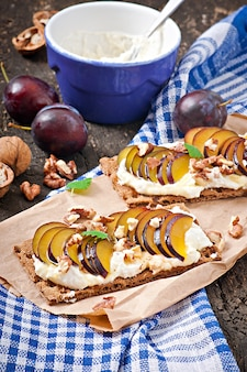 Sandwiches de dieta vegetariana pan crujiente con requesón, ciruelas, nueces y miel en madera vieja