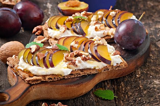 Sandwiches de dieta vegetariana pan crujiente con requesón, ciruelas, nueces y miel en la mesa de madera vieja