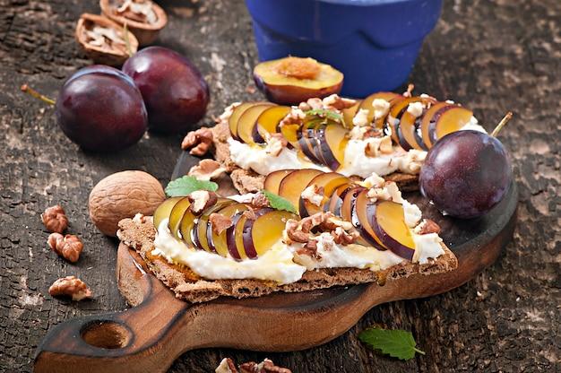 Sandwiches de dieta vegetariana pan crujiente con requesón, ciruelas, nueces y miel sobre madera vieja
