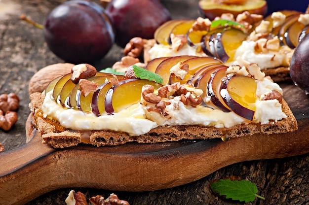 Sandwiches de dieta vegetariana pan crujiente con requesón, ciruelas, nueces y miel sobre tabla de madera vieja