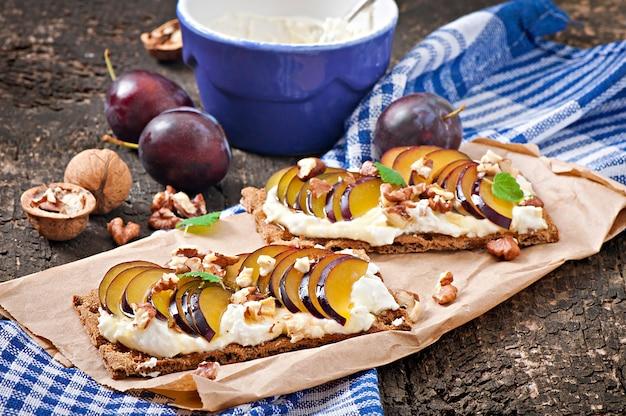 Sandwiches de dieta vegetariana pan crujiente con requesón, ciruelas, nueces y miel