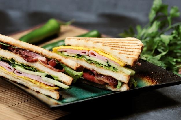 Sandwiches de forma triangular con jamón y tortilla en un plato