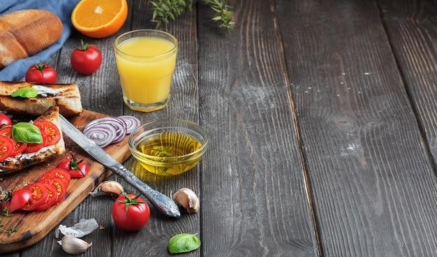 Sándwiches frescos baguette, tomates, verduras y aceite de oliva, ingredientes para hacer un sándwich vegano, primer plano. zumo de naranja recién exprimido en un vaso fondo de madera oscura, copia espacio para texto