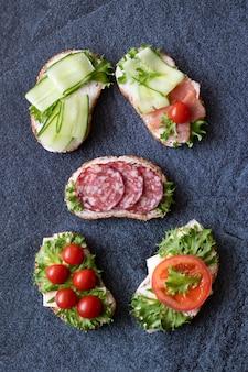 Sandwiches frescos con salchichas, queso, tocino, tomates, lechuga, pepinos en la oscuridad