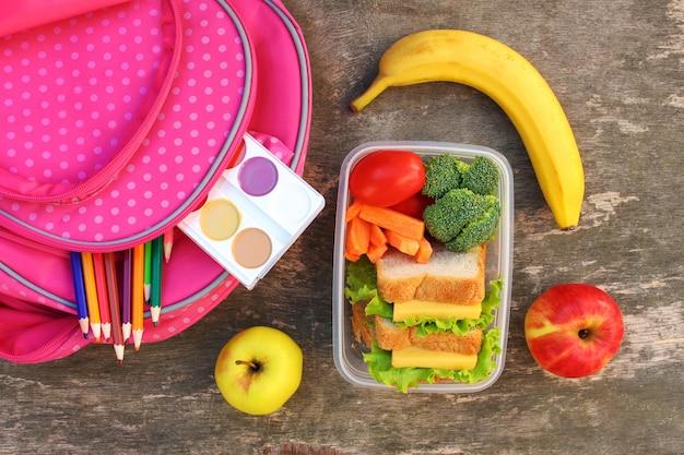 Sandwiches, frutas y verduras en caja de comida, mochila
