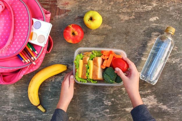Sándwiches, frutas y verduras en caja de comida.