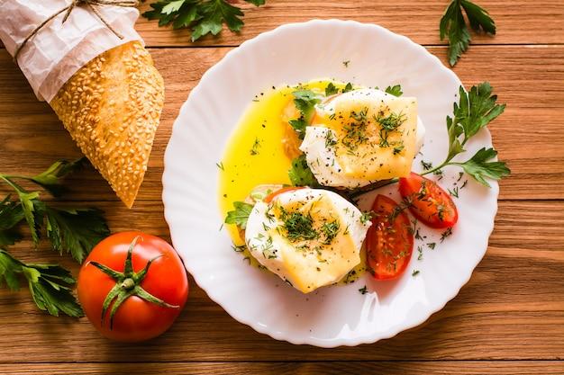Sandwiches con huevo escalfado, tomate, perejil y queso. vista superior