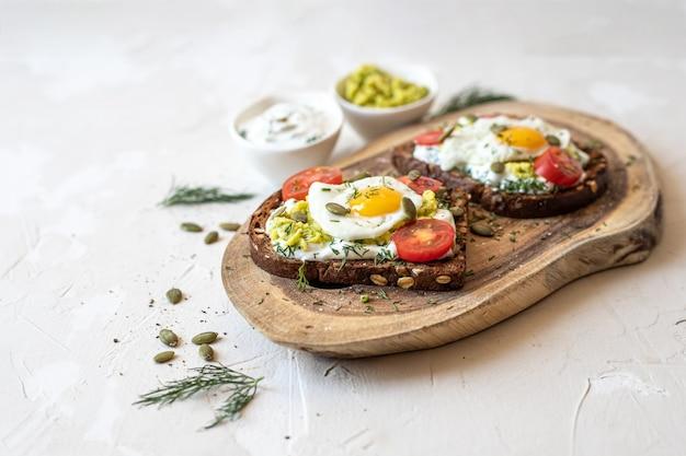 Sándwiches con huevos de codorniz fritos, sobre una tabla de madera. enfoque selectivo