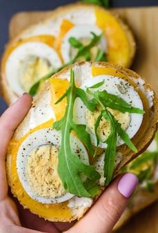 Sándwiches con huevos duros, tomates amarillos y rúcula.