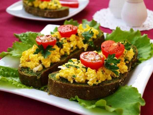 Sandwiches con huevos revueltos y tomates cherry en pan casero con ortigas