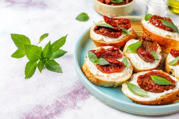 Sándwiches italianos: bruschetta con queso, tomates secos y albahaca.