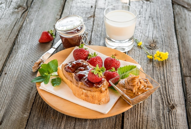 Sandwiches con mantequilla de maní, mermelada y frutas frescas.