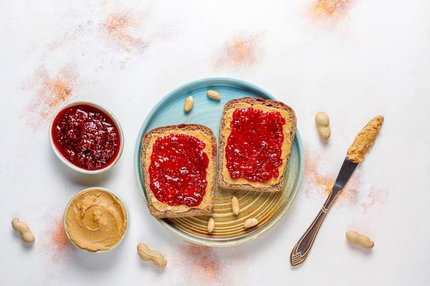 Sándwiches de mantequilla de maní o tostadas con mermelada de frambuesa.