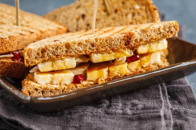 Sándwiches de mantequilla de maní con plátano en placa oscura. concepto de desayuno vegano saludable. macro