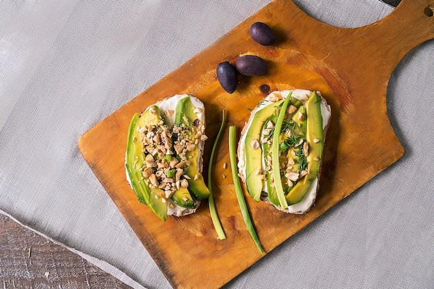Sándwiches o tapas con pan, queso crema, vegetales y deliciosos ingredientes. comida saludable para el almuerzo o el desayuno. copie espacio para su texto. endecha plana.