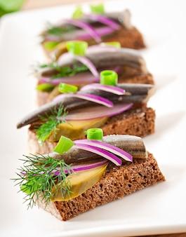 Sandwiches de pan de centeno con arenque, cebolla y hierbas.