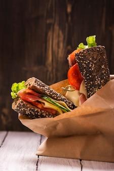Sándwiches de pan de centeno con jamón, queso y verduras.