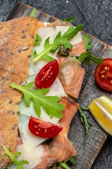Sándwiches con pan ciabatta casero, pescado salmón salado, queso parmesano, alcaparras, tomates cherry y rúcula, fondo de receta de comida. de cerca,
