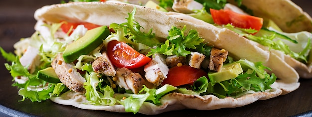 Sandwiches de pan de pita con carne de pollo a la parrilla, aguacate, tomate, pepino y lechuga servidos en una mesa de madera