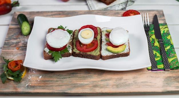 Sándwiches de pan con queso mozarella, huevo cocido y tomates.